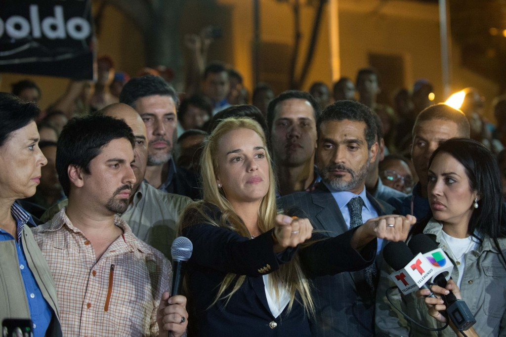 The wife of jailed opposition leader Leopoldo Lopez, Lilian Tintori (C), reacts during press conference in Caracas on September 10, 2015. Jailed Venezuelan opposition leader Leopoldo Lopez was sentenced to nearly 14 years in prison for inciting violence during deadly protests in 2014. The popular dissident, a US-trained economist who has been held at a military prison since February 2014, is accused of inciting violence against the government of President Nicolas Maduro and attempting to force his ouster. AFP PHOTO/ FEDERICO PARRA