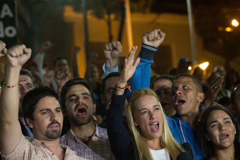 The wife of jailed opposition leader Leopoldo Lopez, Lilian Tintori (2-R) reacts  during press conference in Caracas on September 10, 2015. Jailed Venezuelan opposition leader Leopoldo Lopez was sentenced to nearly 14 years in prison for inciting violence during deadly protests in 2014. The popular dissident, a US-trained economist who has been held at a military prison since February 2014, is accused of inciting violence against the government of President Nicolas Maduro and attempting to force his ouster. AFP PHOTO/ FEDERICO PARRA