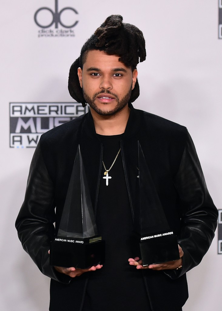 The Weeknd poses with his award at the 2015 American Music Awards in Los Angeles, California on November 22, 2015. AFP PHOTO / FREDERIC J. BROWN / AFP / FREDERIC J. BROWN