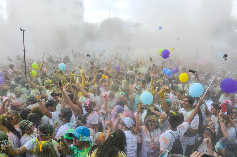 Runners dance covered in coloured powder after taking part in the Color Run of Caracas, on November 22, 2015. AFP PHOTO/FEDERICO PARRA / AFP / FEDERICO PARRA
