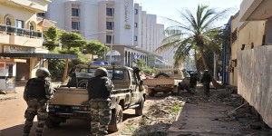 Malian troops take position outside the Radisson Blu hotel in Bamako on November 20, 2015. Gunmen went on a shooting rampage at the luxury hotel in Mali's capital Bamako, seizing 170 guests and staff in an ongoing hostage-taking that has left at least three people dead. AFP PHOTO / HABIBOU KOUYATE / AFP / HABIBOU KOUYATE