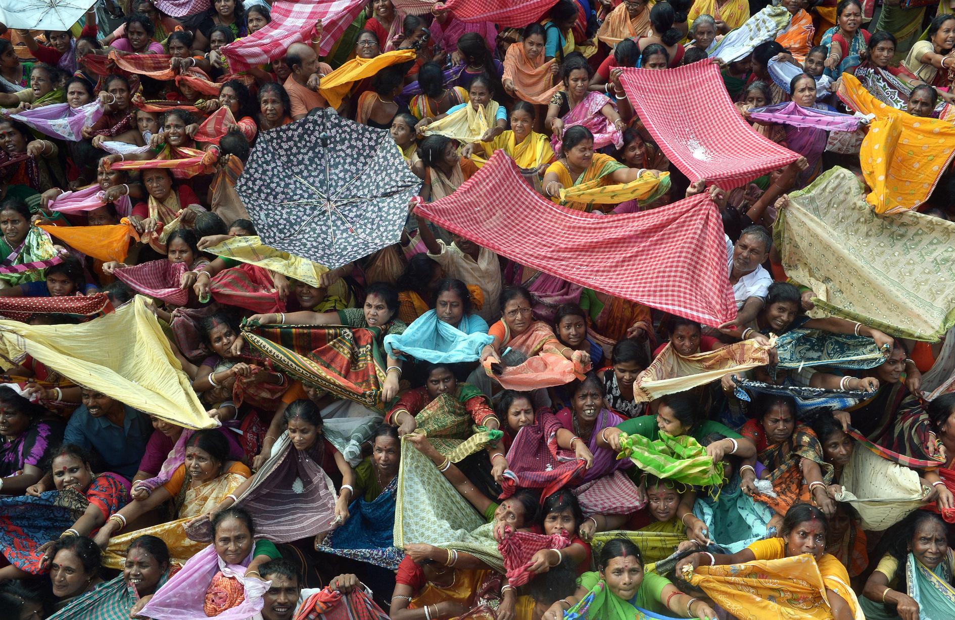 Devotos hindúes recogen el arroz como ofrendas, distribuidas por la autoridad del templo con motivo del festival 'Annakut' en Calcuta. AFP Dibyangshu SARKAR