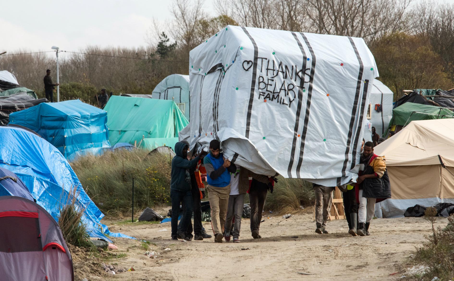 Hombres migrantes mueven una tienda de campaña en el New Jungle, campamento de inmigrantes en Calais, Francia. AFP DENIS CHARLET