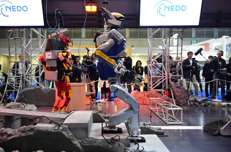 A humanoid robot HRP-2, produced by Kawada, walks amongst mock debris scattered on the ground during a demonstration of how the robot would maneuver within a disaster area at the annual International Robot Exhibition in Tokyo on December 2, 2015. Government sponsored NEDO demonstrated various kinds of robots designed for working in disaster areas. AFP PHOTO / Yoshikazu TSUNO / AFP / YOSHIKAZU TSUNO