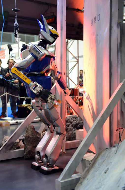 A humanoid robot HRP-2, produced by Kawada, opens a door during a demonstration of how the robot would maneuver within a disaster area at the annual International Robot Exhibition in Tokyo on December 2, 2015. Government sponsored NEDO demonstrated various kinds of robots designed for working in disaster areas. AFP PHOTO / Yoshikazu TSUNO / AFP / YOSHIKAZU TSUNO
