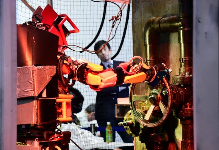 Humanoid robot Jaxon, produced by Tokyo University, turns a handle of a valve during a demonstration of how the robot would work within a disaster area at the annual International Robot Exhibition in Tokyo on December 2, 2015. Government sponsored NEDO demonstrated various kinds of robots designed for working in disaster areas. AFP PHOTO / Yoshikazu TSUNO / AFP / YOSHIKAZU TSUNO
