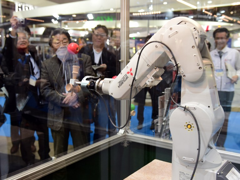 An industrial robot made by Mitsubishi Electric plays a traditional Japanese game called kendama, similar to a cup-and-ball game, during a demonstration at the annual International Robot Exhibition in Tokyo on December 2, 2015. Kendama is Japanese traditional game using a wooden toy with three cups and a spike which sticks into a hole in the ball which is connected with a string. Some 450 companies and organisations displayed their latest robots and 5,000 people were expecting to visit a four-day event. AFP PHOTO / Yoshikazu TSUNO / AFP / YOSHIKAZU TSUNO