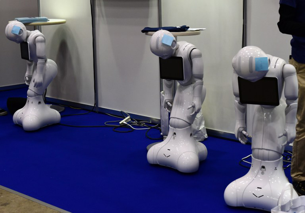 "Japan's telecom giant Softbank's ""Pepper"" humanoid robots 'rest' before the start of the annual International Robot Exhibition in Tokyo on December 2, 2015. Some 450 companies and organisations are displaying their latest robots with 5,000 people expected to visit during the four-day event. AFP PHOTO / Yoshikazu TSUNO / AFP / YOSHIKAZU TSUNO"