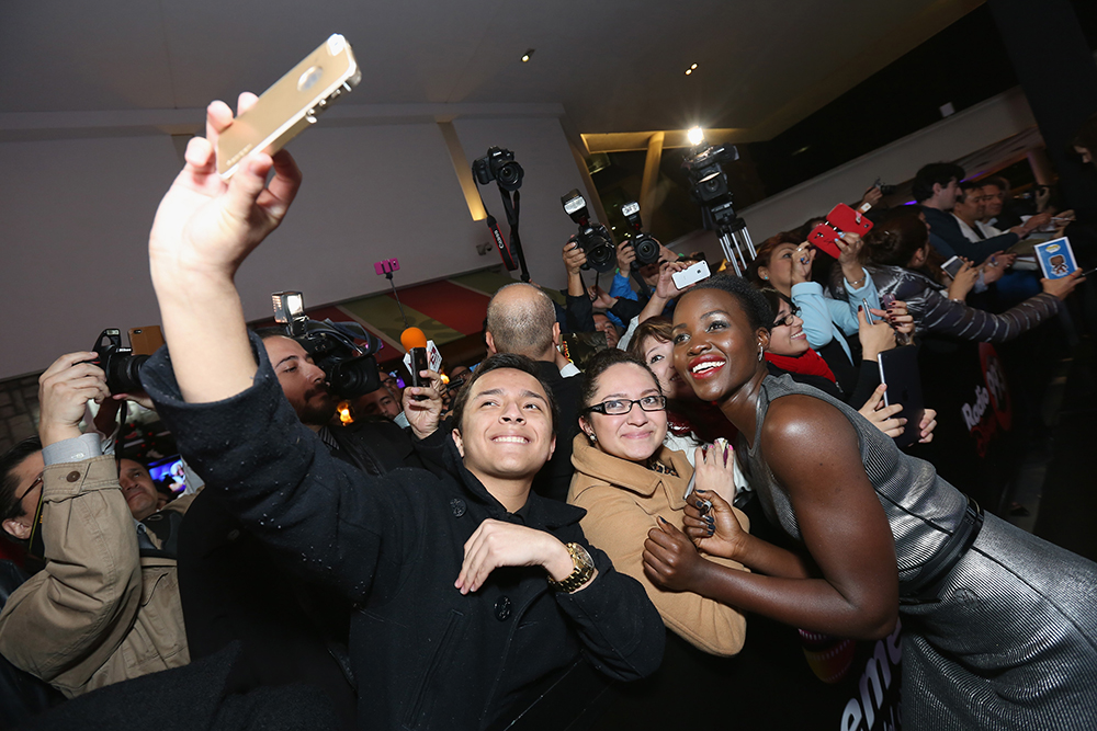 "MEXICO CITY, MEXICO - DECEMBER 08: Actress Lupita Nyong'o signs autographs and takes selfies with fans during the ""Star Wars: The Force Awakens"" Mexico City premiere fan event at Cinemex Antara Polanco on December 8, 2015 in Mexico City, Mexico.   Victor Chavez/Getty Images for Walt Disney Studios'/AFP"