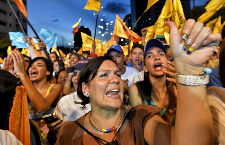Supporters of the opposition Movement of Democratic Unity (MUD) party attend the campaign closing rally on December 3, 2015 in Caracas, Venezuela. Polls suggest the coalition that includes opposition leader Henrique Capriles' party could win a majority in the National Assembly for the first time since late socialist leader Hugo Chavez took power in 1999. AFP PHOTO / LUIS ROBAYO / AFP / LUIS ROBAYO