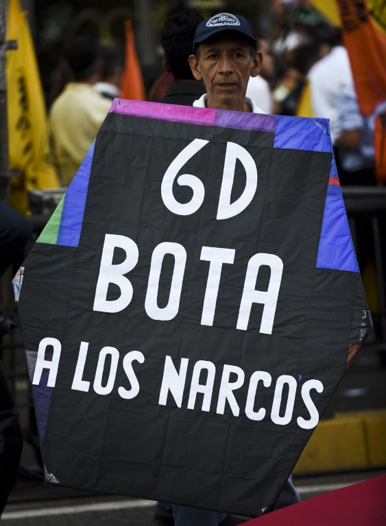 """A man holds a banner reading: """"6D Throw away narcos (drug-traffickers)"""" during the campaign closing rally of the opposition Movement of Democratic Unity (MUD)on December 3, 2015 in Caracas, Venezuela. Polls suggest the coalition that includes opposition leader Henrique Capriles' party could win a majority in the National Assembly for the first time since late socialist leader Hugo Chavez took power in 1999. AFP PHOTO / LUIS ROBAYO / AFP / LUIS ROBAYO"""